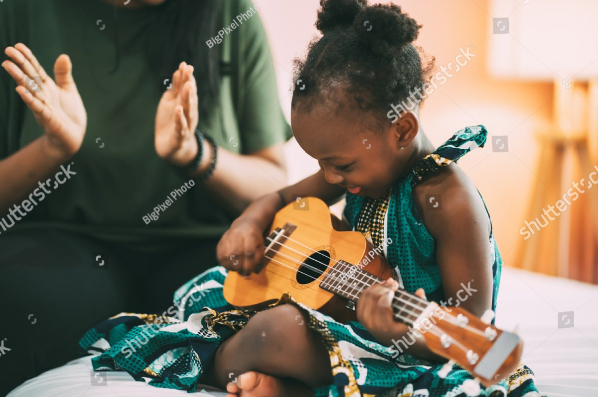 Happy mom clapping while her little daughter playing guitar and singing